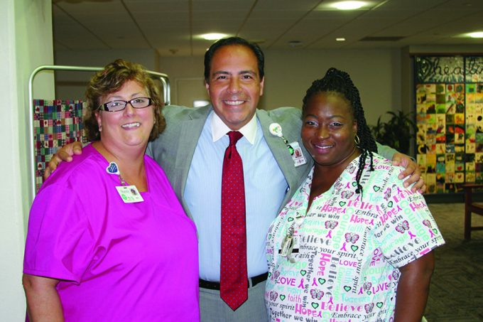 During a flu vaccination event, Ed Jimenez visited with UF Health Shands Occupational Health Services staff: (left) Beverly Hernandez, R.N., and Iechia Houston, office representative.